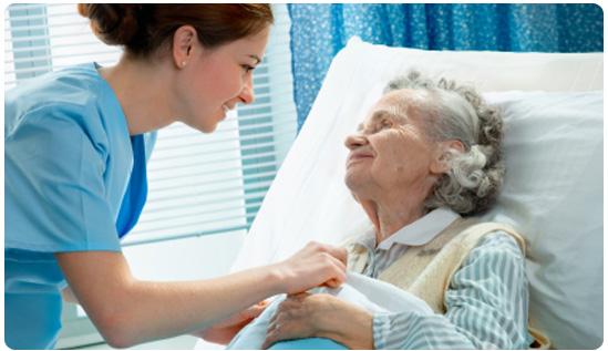 Pflegehelferin am Patientenbett